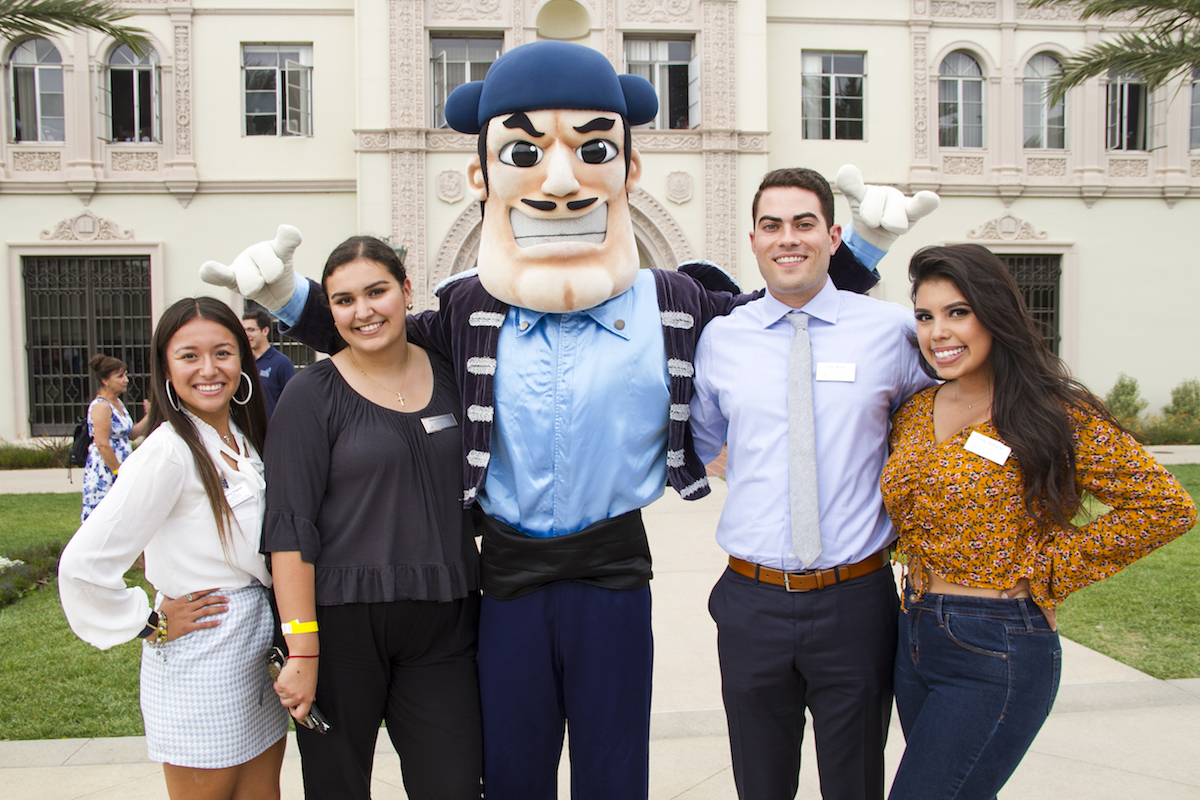 Four students stand with Diego Torero