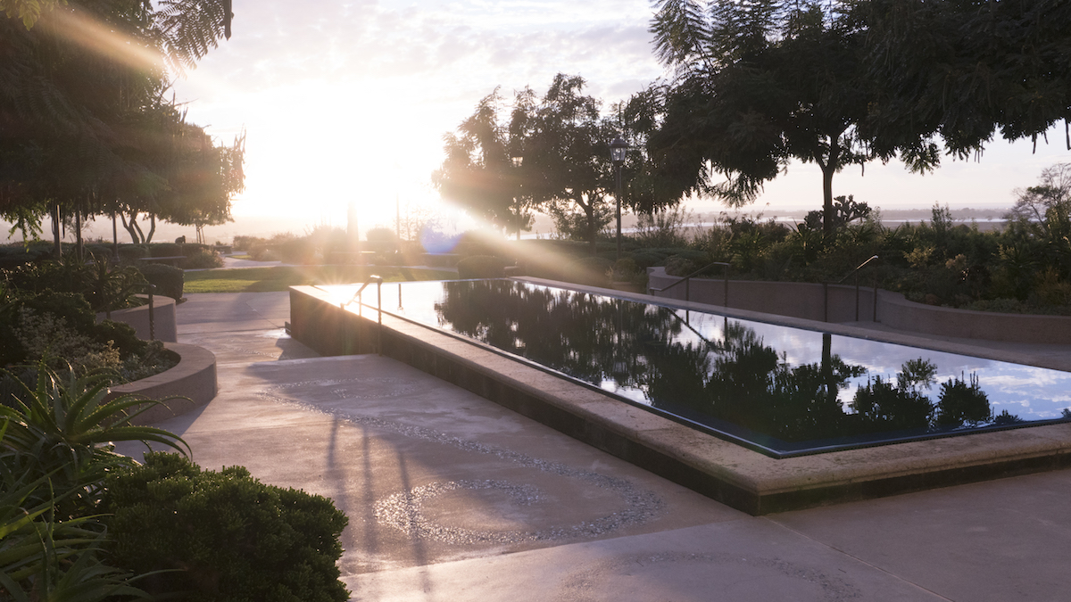 A setting sun casts a glare over the reflecting pool in the Garden of the Sea.