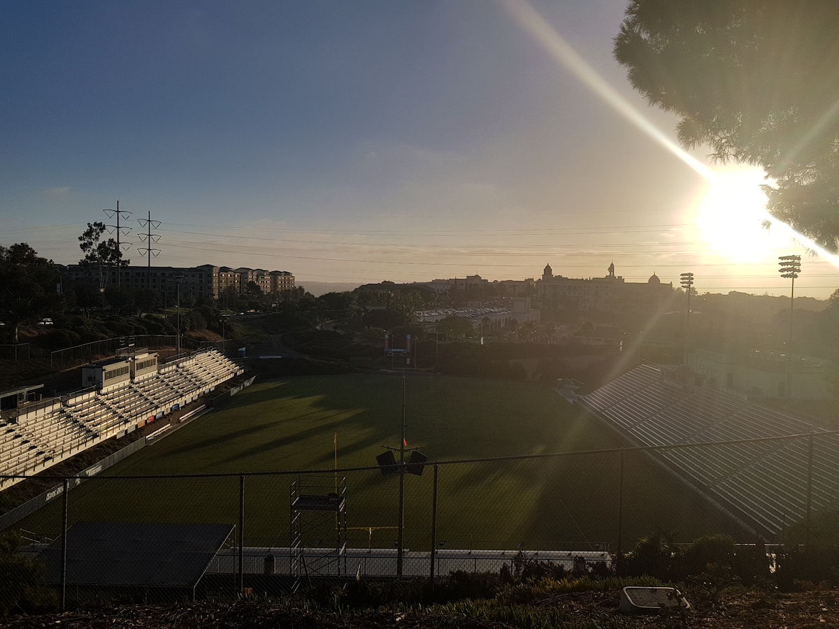 The sun shines bright on the right side of the photo, looking west over Torero Stadium and campus.