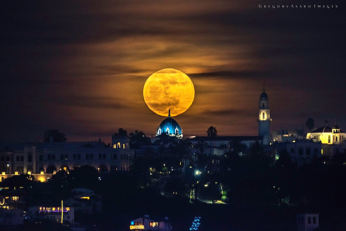 An orange moon silhouettes the Virgin Mary on top of the Immaculata Church at night