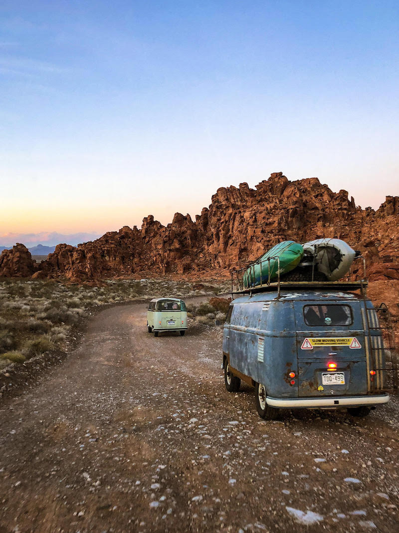 Photo looking out at desert landscape, two vans with kayaks on the roof head down a dirt road.