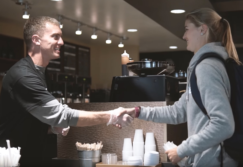 New Men's Basketball Head Coach Sam Scholl meets a student-athlete while serving up orders as a barista for the day.
